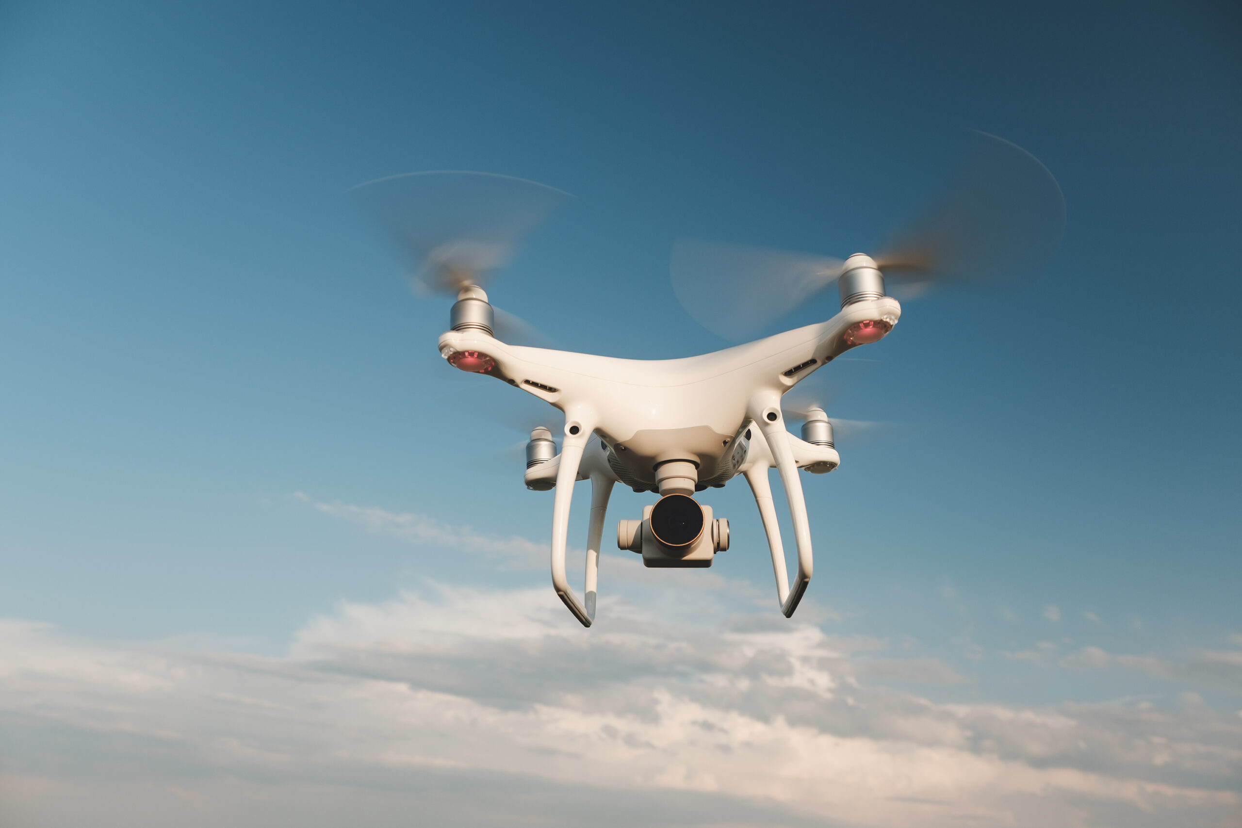 white drone hovering bright blue sky scaled